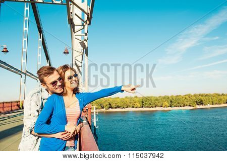 Cheerful Couple In Love On The Bridge Pointing Away