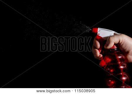 A Human Hand With A Spray Gun Sprays Water On A Dark Background