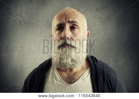 portrait of doleful senior man over dark wall