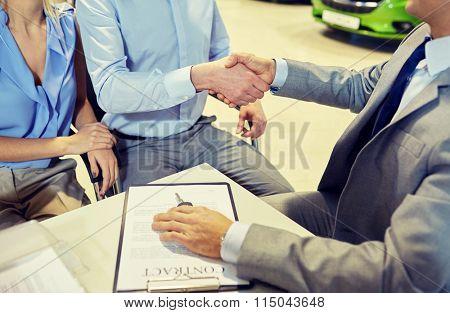 handshake of customer and car dealer in auto salon