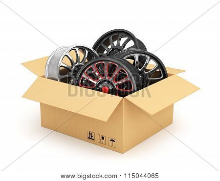 Open Cardboard Box With Car Rims On White Background. Auto Parts.
