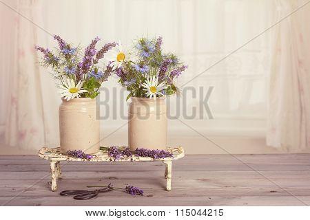 Flower arrangement in vintage pots in window