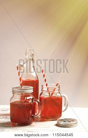 Raspberry drinks in glass cups with drinking straws