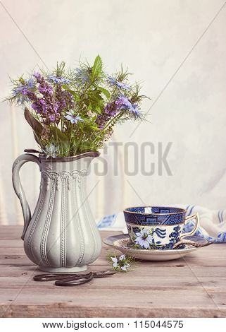 Flowers in antique jug with cup of tea