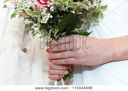 Hands of the bride with a bouquet of flowers.