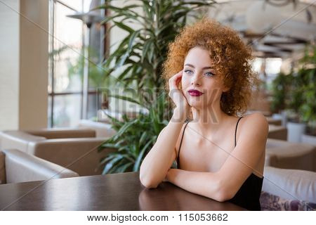 Portrait of a pensive redhead woman sitting at the table in restaurant