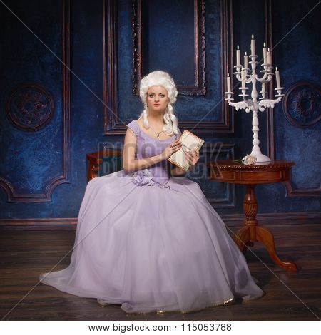 Woman In Historic Baroque Style Dress And White Wig With A Book In Their Hands
