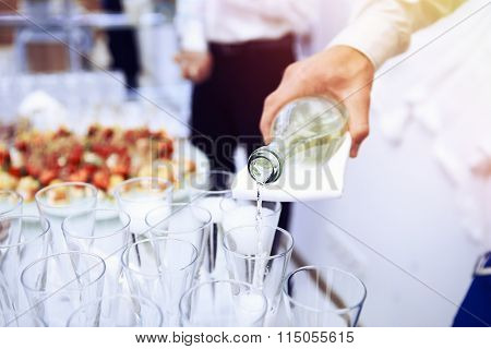 Waiter pours white wine in wineglass