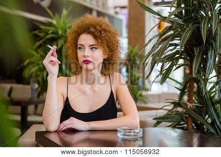Thoughtful redhead woman with curly hair smoking in restaurant