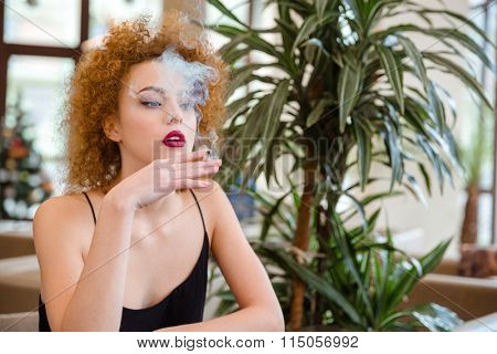 Portrait of a redhead woman with curly hair smoking in restaurant