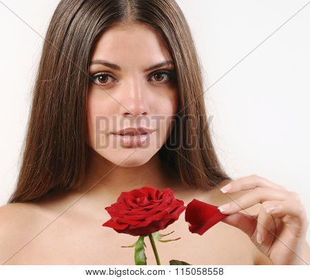 Cute Beautiful Woman Tears Off Petals Of Red Rose And Looking At Camera