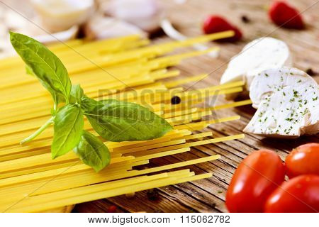 closeup of a pile of uncooked spaghetti, some raw mushrooms, some cherry tomatoes and some other ingredients to prepare a meal on a wooden table