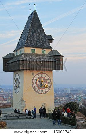 people are walking nearly city clock tower in Graz, Austria