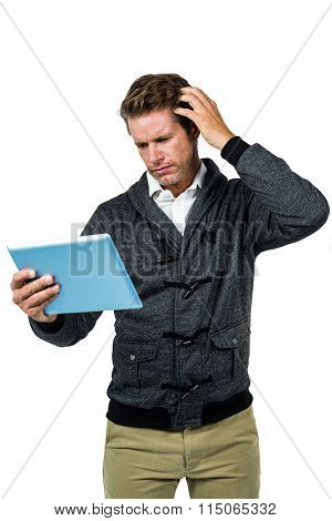 Confused man with digital tablet standing against white background