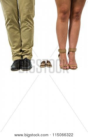 Low section of couple amidst baby footwear over white background