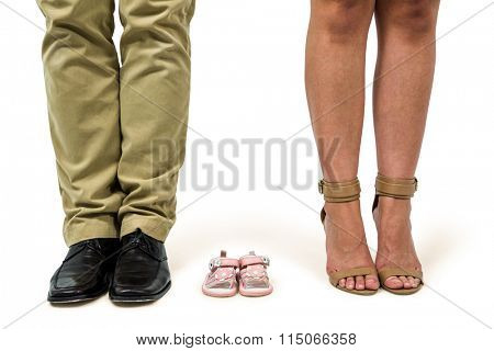 Low section of man and woman amidst baby shoes over white background