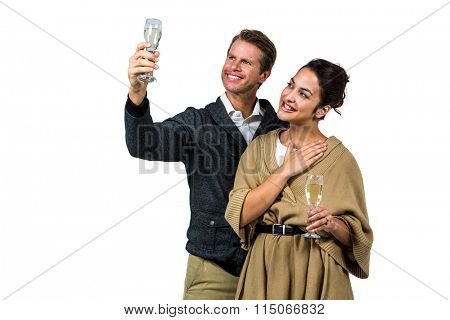Cheerful couple with champagne flute against white background