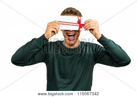 Cheerful man hiding face with gift against white background