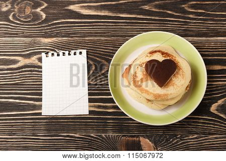 heart-shaped pancakes with card on wooden table