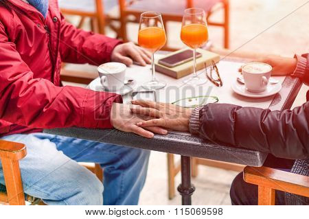 Couple of lovers holding their hands at table bar restaurant for Valentine's day