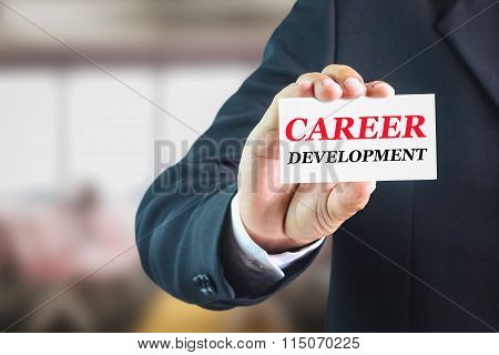 Businessman holding a white sign with the message CAREER DEVELOPMENT.