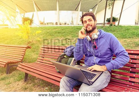 Young Freelance Man Using Mobile Phone And Laptop Pc