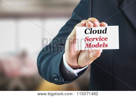Businessman holding a white sign with the message cloud service models.