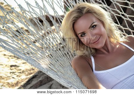 Blond woman relax in a hammock. Smiling and beautiful