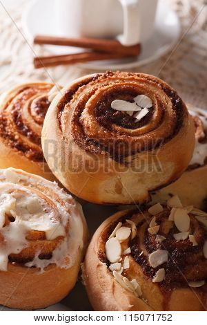 Freshly Baked Cinnamon Rolls With Icing And Almonds Macro. Vertical