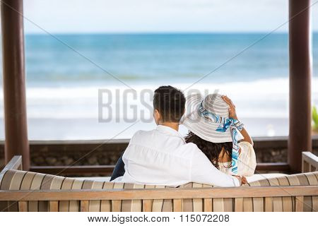 Embracing couple enjoying the view of the azure blue sea, back view