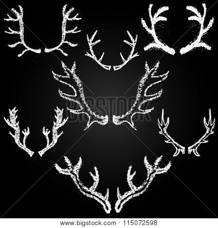 Set Of Chalk Painted Antlers On A Black Chalkboard.