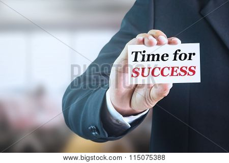 Businessman holding a white sign with the message time for success.