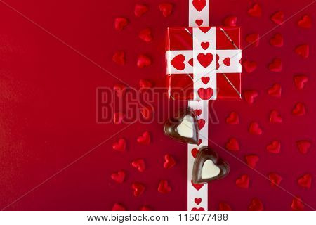Gift And Chocolate And Red Hearts On Red