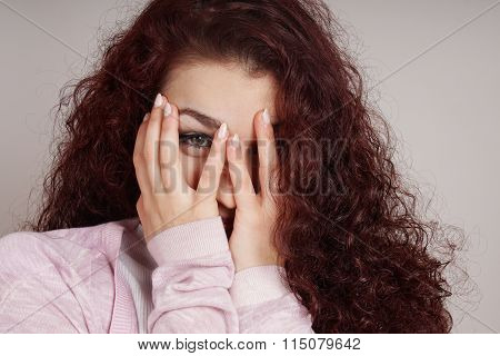 young woman peeking through fingers