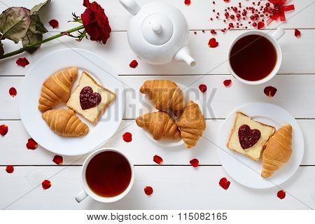 Romantic breakfast for Valentines day with toasts, heart shaped jam, croissants, rose petals and tea