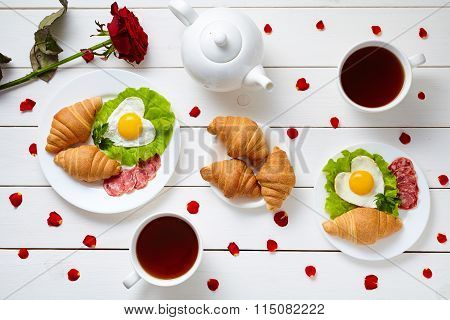 Breakfast for Valentines day with heart shaped eggs, salad, croissants, rose petals and tea on white