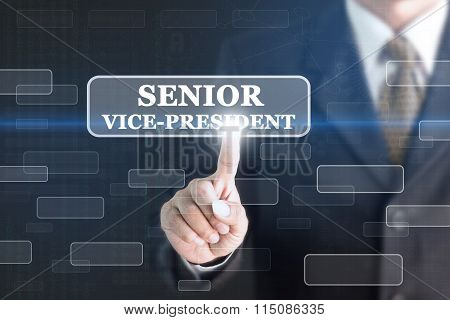 Businessman pressing SENIOR VICE-PRESIDENT concept button.