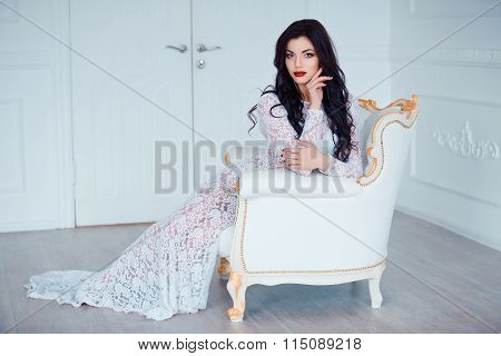 Perfect, sexy young woman wearing seductive white dress sitting on luxury vintage chair