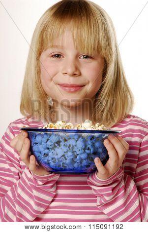 Little blonde girl eating popcorn.