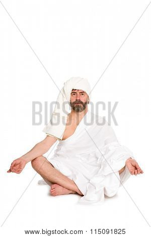 man sitting in the lotus position dressed in traditional clothes of bath. From a series of Russian bath
