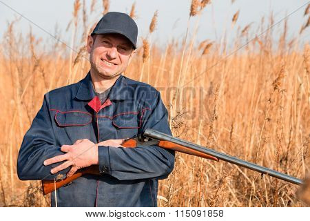 Smiling man on a hunt among autumn grass