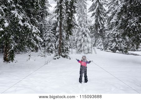 Girl ski suit throwing snow in the air
