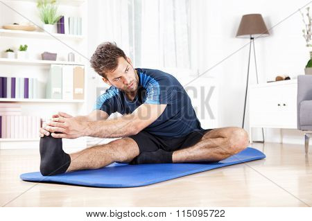 Gorgeous Man Performing Hamstring Stretch At Home