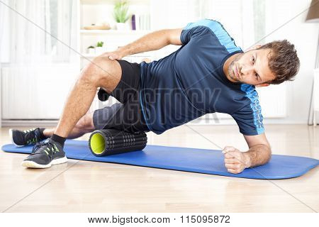 Athletic Man In Side Planking Using Foam Roller