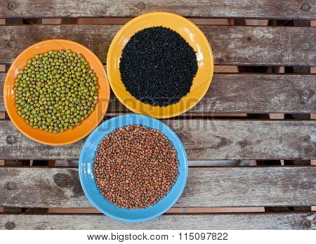 Three Bowls With Different Seeds On Wooden Background