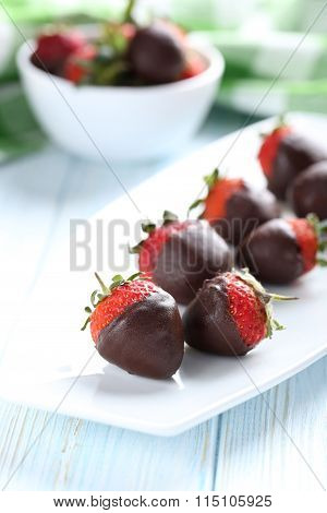 Fresh Strawberries Dipped In Dark Chocolate On Blue Wooden Background