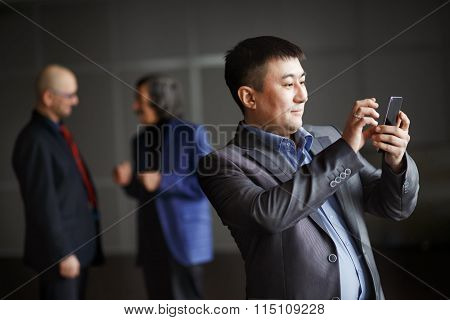 Businessman holding mobile smart phone using app texting sms message, preparing video call,  checkin