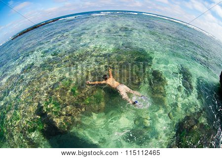 Young man swim in transparent beach in Ly Son island, Quang Ngai, Vietnam