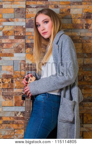 Beautiful young girl in overcoat and jeans posing with guitar on brick background