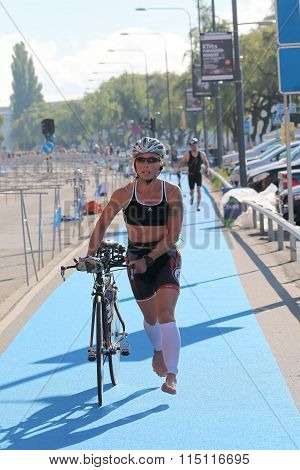 Woman Running Barefoot With Bicycle In The Triathlon Transition Zone